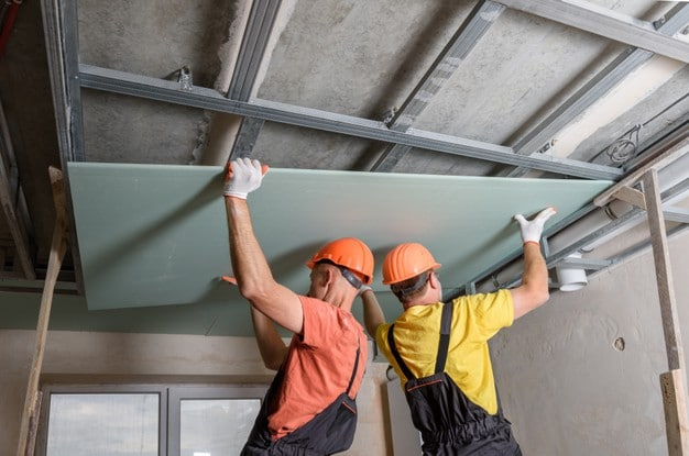 workers-are-lifting-plasterboard-further-attaching-ceiling_191163-1454